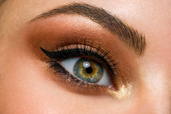 Beautiful female eye with brown, shiny makeup. Fashionable brown makeup. Macro image of a woman's eye.