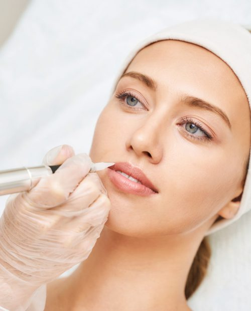 Permanent makeup. Beauty spa procedure. young woman. Face tattoo. Lip micropigmentation. Professional face microblading. Female cosmetology device. Copyspace. Mouth treatment. Dermatology